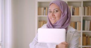 Nahaufnahmeporträt der jungen hübschen moslemischen Ärztin im hijab, das einen Laptop betrachtet Kamera nett herein lächelnd hält stock footage
