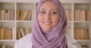 Nahaufnahmeporträt der jungen hübschen moslemischen Ärztin im hijab, das Kamera glücklich lächelnd in der Bibliothek betrachtet stock video footage