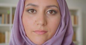 Nahaufnahmeporträt der jungen hübschen moslemischen Studentin im hijab, das Kamera nett zuhause lächelnd in der Bibliothek betrac stock video footage