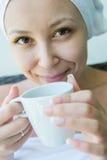 Nahaufnahmeporträt der jungen lächelnden Frau mit der Kappe des Kaffees Stockfoto