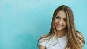 Nahaufnahmeporträt der jungen lächelnden und lachenden Frau, die Kamera auf blauem Hintergrund untersucht Lizenzfreie Stockbilder