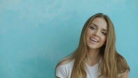 Nahaufnahmeporträt der jungen lächelnden und lachenden Frau, die Kamera auf blauem Hintergrund untersucht stock video