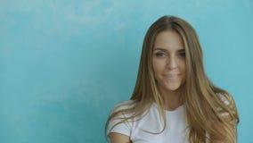 Nahaufnahmeporträt der jungen lächelnden und lachenden Frau, die Kamera auf blauem Hintergrund untersucht stock footage