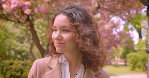 Nahaufnahmeporträt der jungen langhaarigen gelockten kaukasischen Frau, welche die Kamera draußen steht im Park betrachtet stock video