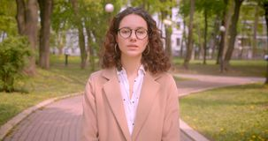 Nahaufnahmeporträt der jungen langhaarigen gelockten kaukasischen Studentin in den Gläsern, welche die Kamera draußen herein steh stock footage