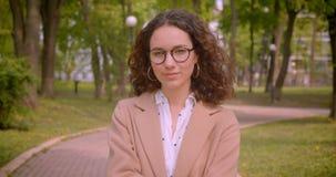 Nahaufnahmeporträt der jungen langhaarigen gelockten kaukasischen Studentin, die ihre lächelt Gläser glücklich, reparierend, die  stock footage