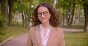 Nahaufnahmeporträt der jungen langhaarigen gelockten kaukasischen Studentin, die ihre lächelt Gläser glücklich, reparierend, die  stock video