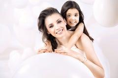 Nahaufnahmeporträt der jungen Mutter mit einer netten Tochter Stockfotografie