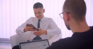 Nahaufnahmeporträt der jungen netten Geschäftsmannvertretungstablette mit grünem Schirm zu seinem Partner unter Verwendung des La stock footage