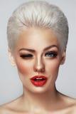 Nahaufnahmeporträt der jungen schönen blonden blinzelnden Frau mit r stockfoto