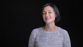Nahaufnahmeporträt der jungen schönen kaukasischen Frau mit dem kurzen schwarzen Haar ihre Lippen leckend und verlockend lächelnd stock footage