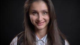 Nahaufnahmeporträt der jungen stilvollen kaukasischen Frau mit dem brunette Haar, das gerade Kamera betrachtet und glücklich läch stockfoto