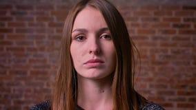 Nahaufnahmeporträt der kaukasischen redheaded Frau mit ernsten Augen aufpassend direkt in Kamera bricken an Hintergrund stock video