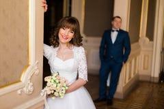 Nahaufnahmeporträt der lächelnden Braut mit dem Hochzeitsblumenstrauß, der auf der Wand am Hintergrund des Bräutigams sich lehnt stockfotografie