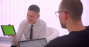 Nahaufnahmeporträt der netten Geschäftsmannvertretungstablette mit grünem Schirm zu seinem Partner unter Verwendung des Laptops i stock video