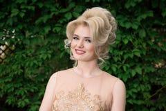 Nahaufnahmeporträt der netten lächelnden Frau auf einem Hintergrund der Natur, ein beige Kleid tragend Sie betrachten Kamera Posi lizenzfreies stockfoto