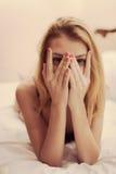Nahaufnahmeporträt der romantischen blonden verlockenden jungen Frau, die im Bett liegt Stockbilder