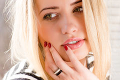 Nahaufnahmeporträt der schönen blonden jungen Frau mit den prallen Lippen auf einem hellen Hintergrund Lizenzfreie Stockbilder