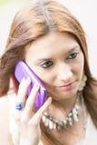 Nahaufnahmeporträt der schönen jungen Frau, die durch intelligentes Telefon spricht Lizenzfreie Stockbilder