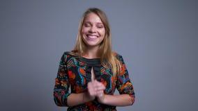 Nahaufnahmeporträt der schönen jungen kaukasischen Frau, die glücklich ihre Arme hält und Kamera mit Aufregung betrachtet stock footage