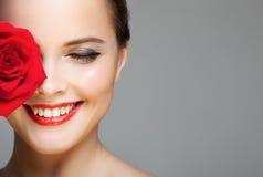 Nahaufnahmeporträt der schönen lächelnden Frau mit Rotrose Stockfotografie