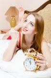 Nahaufnahmeporträt der schönen lustigen jungen blonden Frau der blauen Augen mit Wecker in einem roten Kleid, das auf Bett liegt u Stockfotos