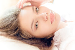 Nahaufnahmeporträt der schönen netten, zarten jungen Frau im Bett, das Kamera auf weißem Hintergrund betrachtet Stockbild