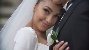Nahaufnahmeporträt der schönen reizend Brunettebraut, die zart ihren Bräutigam umarmt und in camera schaut stock video footage