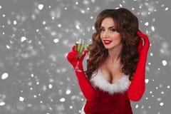 Nahaufnahmeporträt der schönen sexy Frau auf dem grauen Hintergrund mit Glas Champagner und Betrachten der Kamera Stockfotos