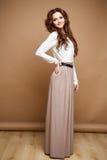 Nahaufnahmeporträt der schönen sexy jungen Frau mit dem langen braunen Haar über braunem Hintergrund Stockbild