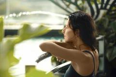 Nahaufnahmeporträt der sexy dünnen Frau im Swimmingpool zwischen grünen Büschen lizenzfreie stockfotografie