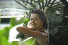 Nahaufnahmeporträt der sexy dünnen Frau im Swimmingpool zwischen grünen Büschen stockbilder