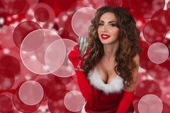Nahaufnahmeporträt der sexy Frau im Weihnachtskleid mit Glas Champagner und Betrachten der Kamera Stockbild