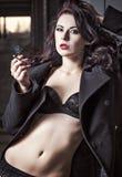 Nahaufnahmeporträt der sexy rauchenden Vampfrau in der Unterwäsche und im Mantel Stockfotografie