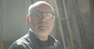 Nahaufnahmeporträt des älteren männlichen Zimmereimeisters, der an der hölzernen Fabrik aufpasst in die Kamera ist ernst und ruhi stock footage