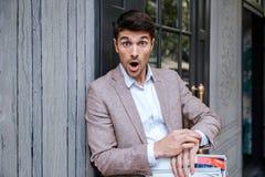Nahaufnahmeporträt des überraschten Mannes, der draußen Uhr betrachtet Lizenzfreie Stockfotos