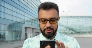Nahaufnahmeporträt des überzeugten ernsten afrikanischen Mannes in den Brillen unter Verwendung des Handys über dem Glasgebäude E stock video footage