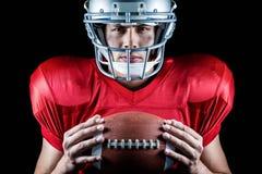 Nahaufnahmeporträt des überzeugten Spielers des amerikanischen Fußballs, der Ball hält Stockfotografie