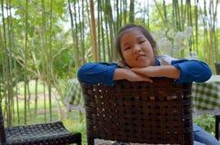 Nahaufnahmeporträt des asiatischen Mädchens sitzen auf Stuhl Stockbilder