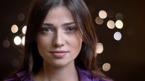 Nahaufnahmeporträt des attraktiven kaukasischen brunette Mädchens, das ruhig in Kamera auf unscharfem Lichthintergrund aufpasst lizenzfreie stockbilder