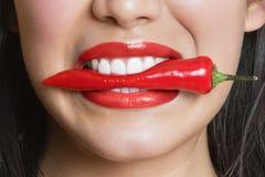 Nahaufnahmeporträt des beißenden roten Pfeffers der hispanischen Frau Stockfoto