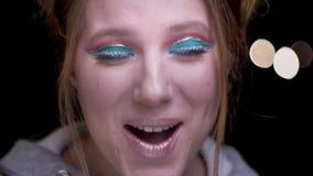 Nahaufnahmeporträt des blonden Mädchens mit dem bunten Make-up, das playfully Überraschung auf unscharfem Lichthintergrund zeigt stock video footage