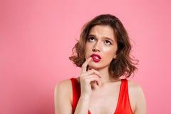 Nahaufnahmeporträt des Denkens der jungen Schönheit mit der roten Lippe Stockbild