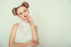 Nahaufnahmeporträt des durchdachten schönen Mädchens mit lustiger Frisur Schlauer und entwerfender Gesichtsausdruck der jungen Fr Lizenzfreie Stockfotografie