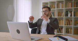 Nahaufnahmeporträt des erwachsenen hübschen kaukasischen Geschäftsmannes in den Gläsern unter Verwendung des Laptops, der im Büro stock video