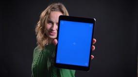 Nahaufnahmeporträt des erwachsenen kaukasischen weiblichen Grasens auf dem Laptop und des Zeigens des blauen Schirmes zur Kamera  stock footage