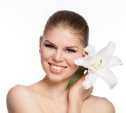 Nahaufnahmeporträt des frohen, lächelnden kaukasischen Mädchens mit weißer Blume in ihrer Hand Stockfotografie