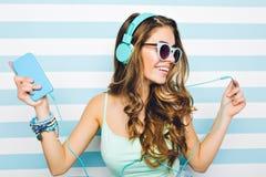 Nahaufnahmeportr?t des frohen M?dchens Musik in den gro?en Kopfh?rern genie?end, Handy in der Hand halten Attraktive junge Frau lizenzfreies stockbild