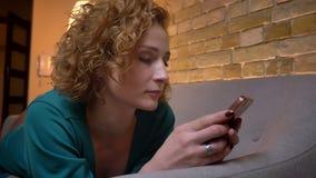 Nahaufnahmeporträt des gelockten Mädchens des Ingwers, das auf Magen auf Sofauhren in Smartphone und in Lächeln in Kamera liegt stock footage