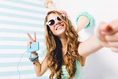 Nahaufnahmeportr?t des gl?ckseligen M?dchens in der Sonnenbrille und die modischen Armb?nder, die mit Frieden aufwerfen, unterzei lizenzfreies stockfoto